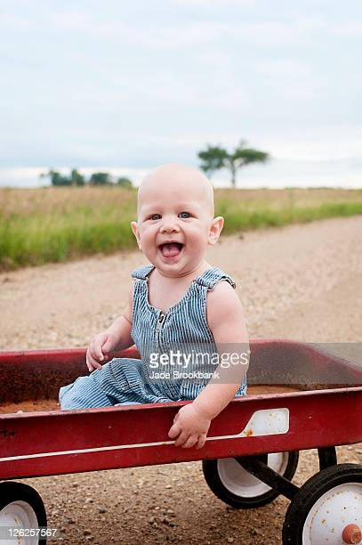 Baby sitting in wagon on dirt road