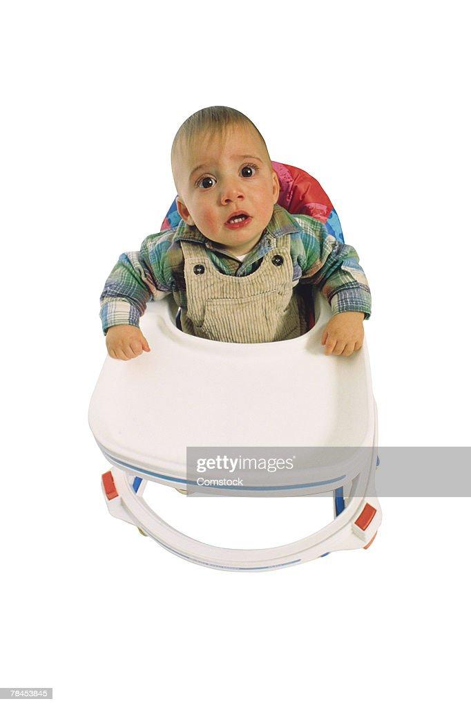 Baby sitting in walker : Stockfoto