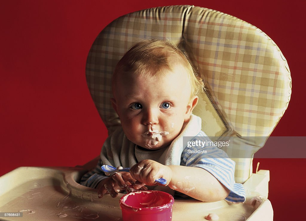 Baby Sitting On A Highchair Holding Spoon With Food On ...