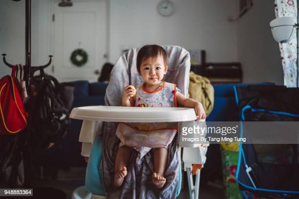 Baby sitting on high chair having snack joyfully.