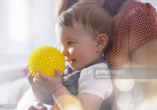 baby sitting on mother's lap holding ball