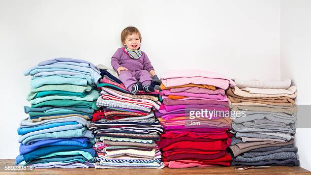 Baby sitting on pile of clothes