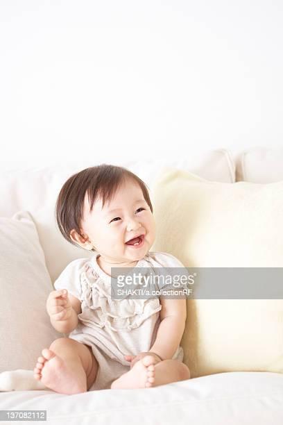 Baby sitting on sofa smiling