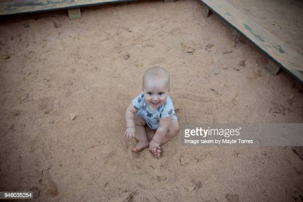 Baby sitting on the sand at the playground