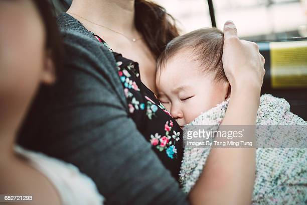 Baby sleeping comfortably under mother's arms