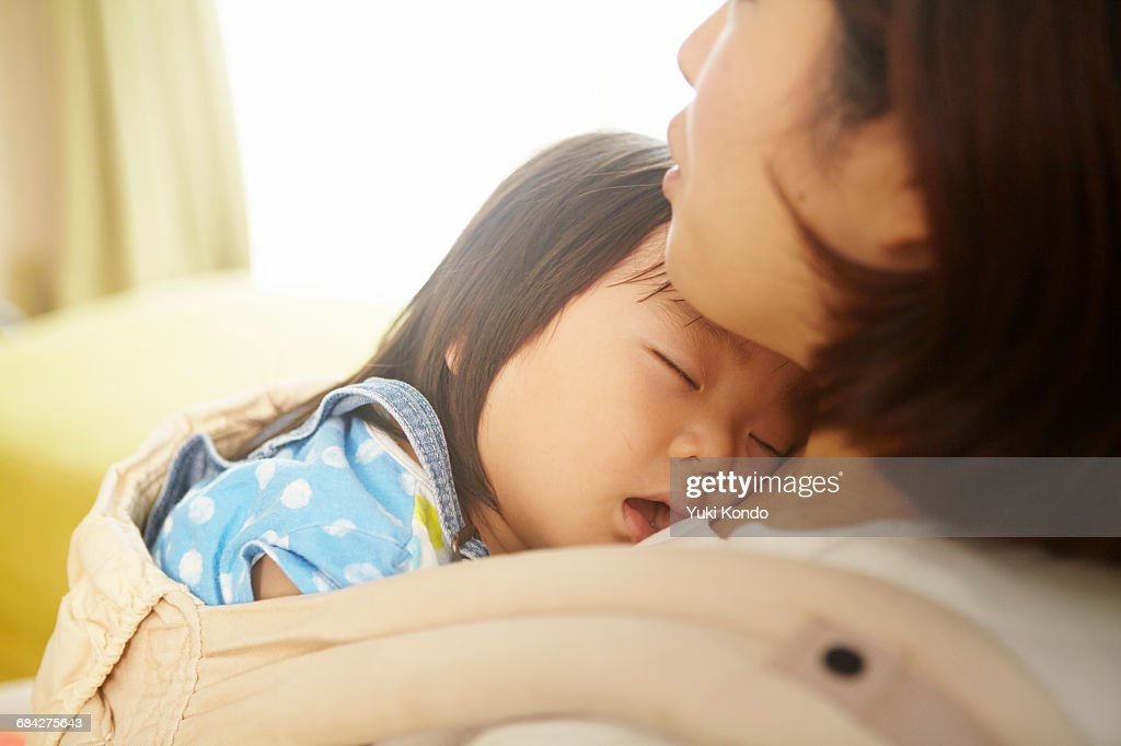 Baby sleeping in a mother holding it. : Stock Photo