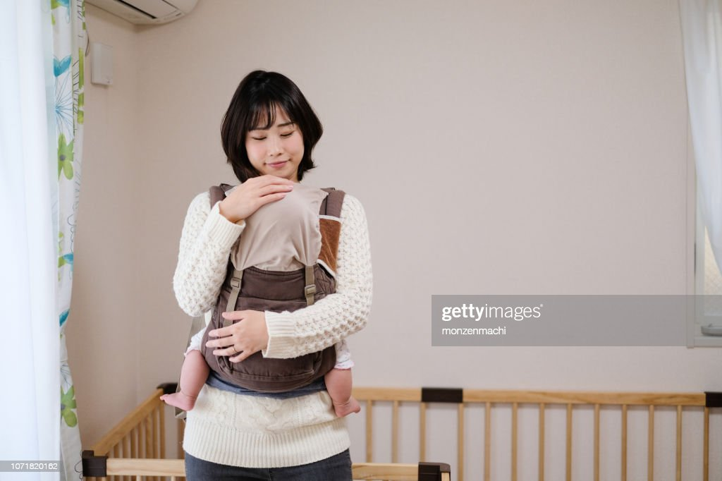 Baby sleeping in arms of mother : Foto stock