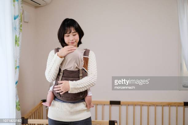 baby sleeping in arms of mother - homemaker stock pictures, royalty-free photos & images