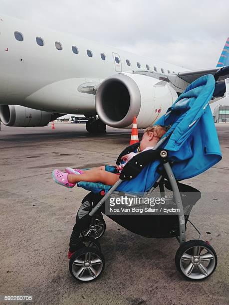 Baby Sleeping In Baby Carriage On Street Against Airplane
