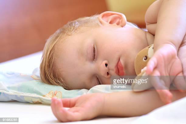 Bebé dormir en la cama con Osito de peluche