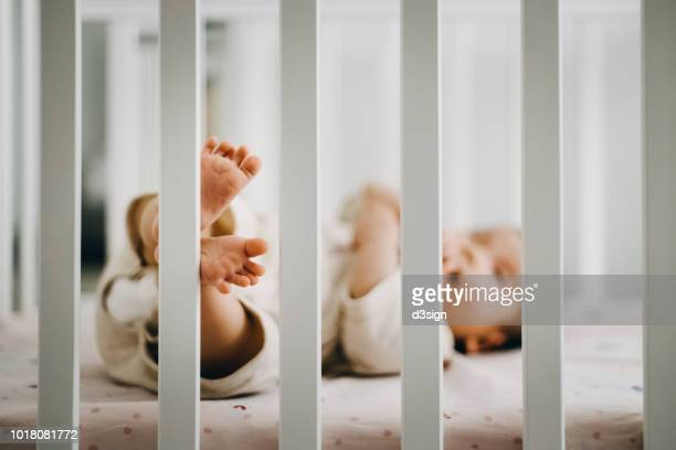 baby sleeping in cot, little feet stepping on the fence of cot - crib stock pictures, royalty-free photos & images