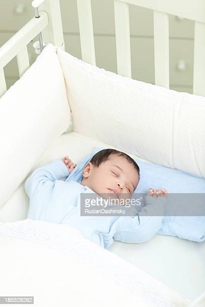 Baby sleeping in crib in white sheets