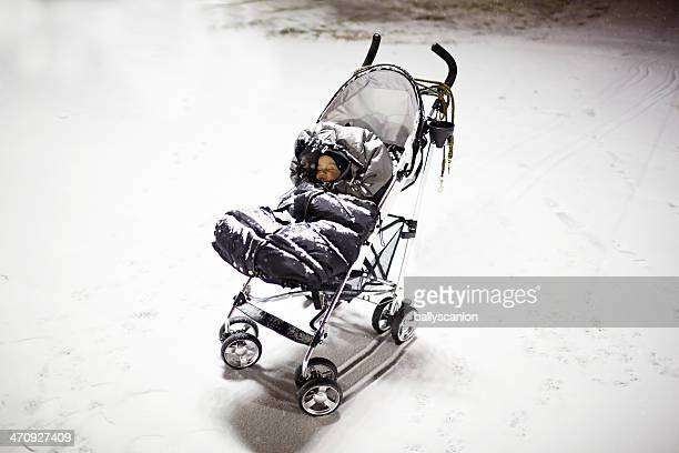 Baby sleeping in stroller, covered in snow