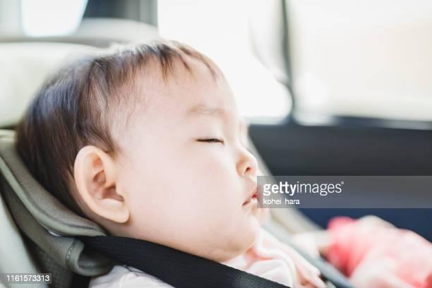 baby schläft auf kindersitz im auto - landfahrzeug stock-fotos und bilder
