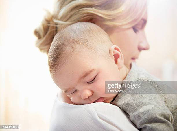 baby sleeping on mother's shoulder - newborn stock pictures, royalty-free photos & images