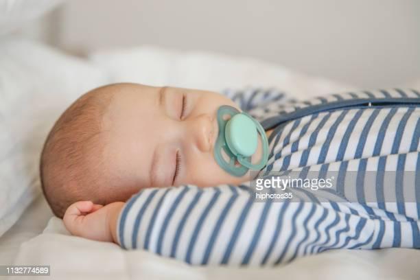 bebê que dorme no quilt branco - bico - fotografias e filmes do acervo