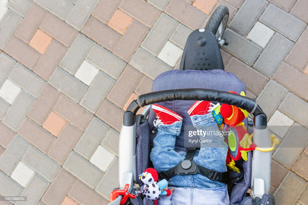 Baby sleeping three-wheel stroller outdoor. Child in bright casual costume lying at big comfortable pram. Parent walking with carriage in city park. View from above : Stock Photo
