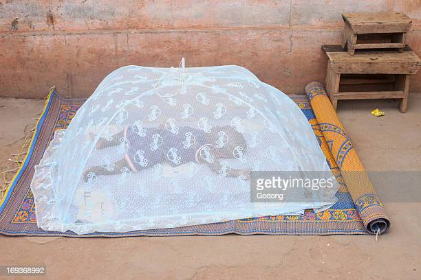 Baby sleeping under a mosquito net Togo