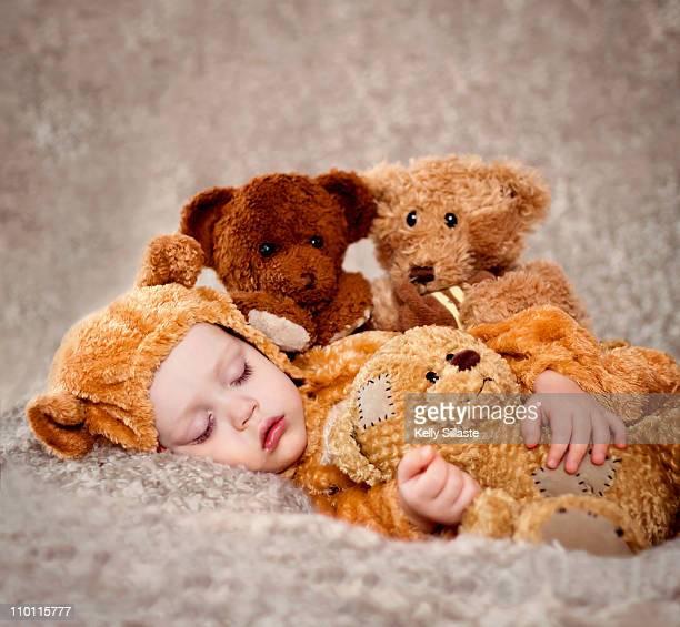 A baby sleeping with soft teddy bears