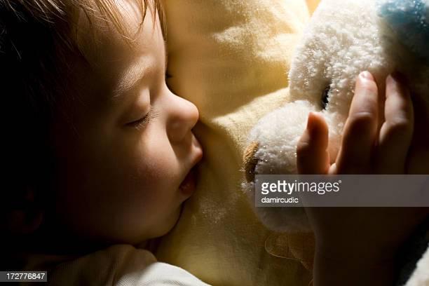 Bébé avec ours en peluche de couchage