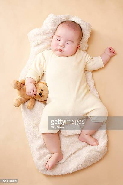 baby (3-6 months) sleeping with teddy bear - baby onesie stock photos and pictures