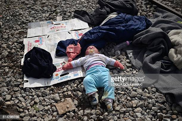 TOPSHOT A baby sleeps near the railway tracks at the makeshift camp of the GreekMacedonian border near the village of Idomeni on March 8 where...