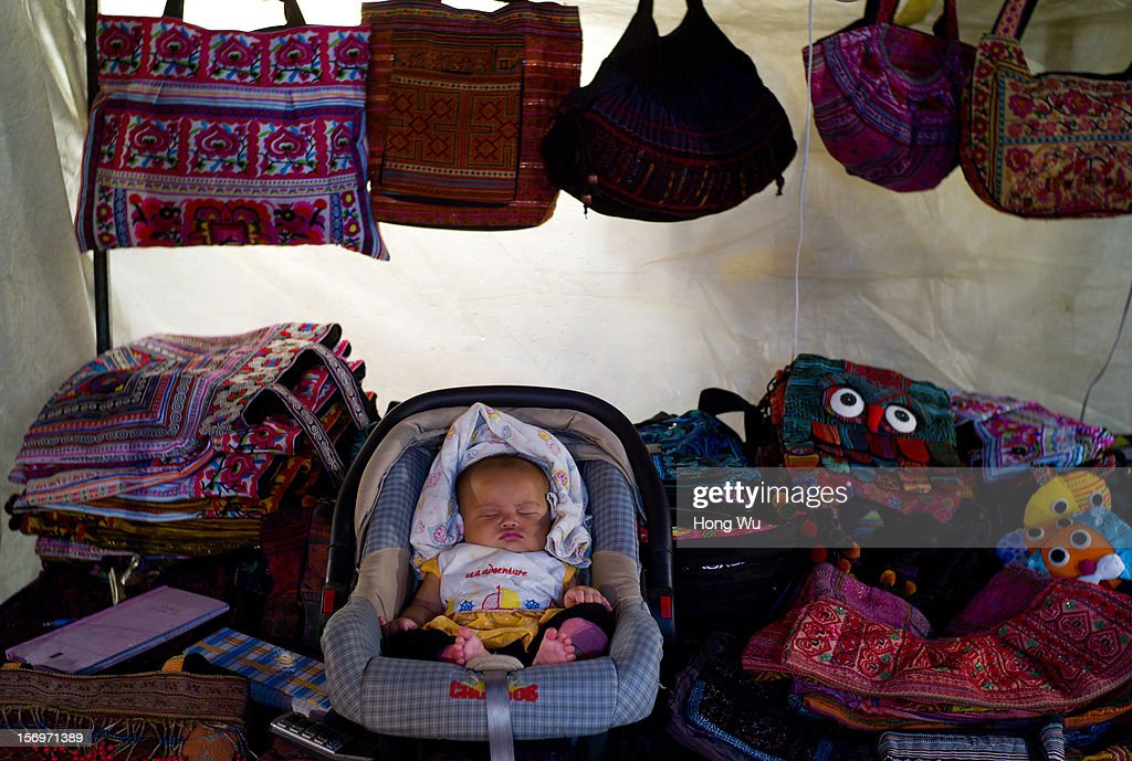 A baby sleeps on a bag stall at Tha Phae Gate on November 26, 2012 in Chiang Mai, Thailand. Chiang Mai is the largest and most culturally significant city in northern Thailand. It's a former capital of the Kingdom of Lanna (1296 - 1768) and was the tributary Kingdom of Chiang Mai from 1774 until 1939. In recent years, it has become an increasingly modern city and has been attracting over 5 million visitors each year, of which between 1.4 million and 2 million are foreign tourists.
