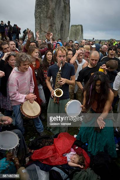 A baby sleeps peacefully as an eclectic mix of partygoers revellers pagans druids and drummers make music and dance within the stone circle of...
