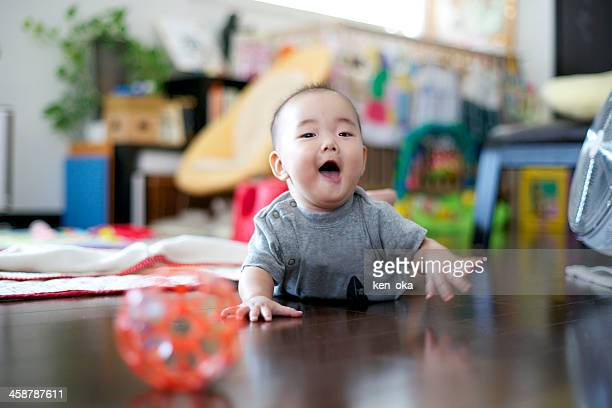 A baby smiles by crawl in room