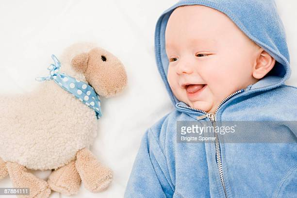 Baby smiling to a sheep