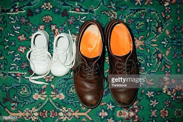 Baby sneakers on the carpeted floor next to a pair of man's dress shoes.