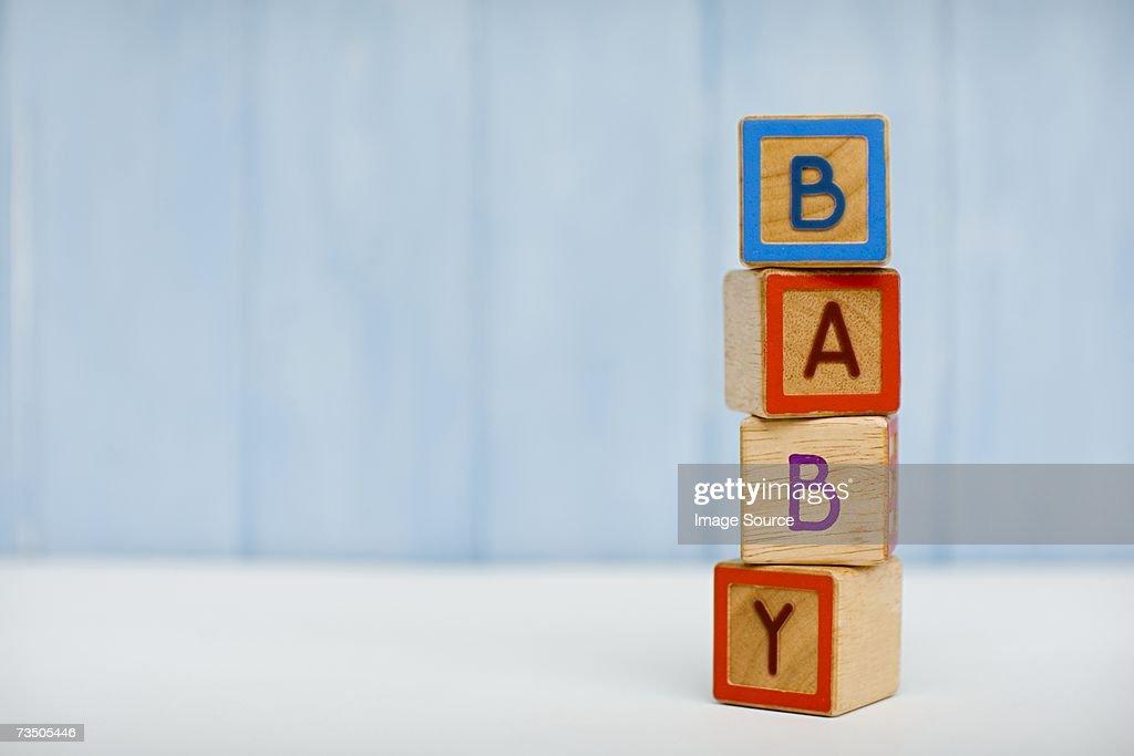 Baby spelt in building blocks : Stock Photo