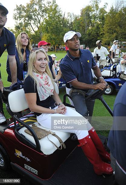 A baby squirrel sits on the thighs of Tiger Woods of the US Team as he follow the play with Lindsey Vonn during the Day One FourBall Matches of The...