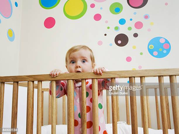 baby standing in crib with surprised expression - funny wake up stock pictures, royalty-free photos & images