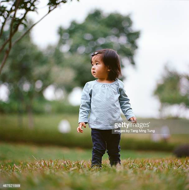 Baby standing on the lawn in park looking away