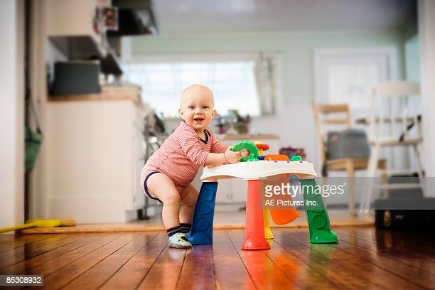 baby stands at play station - one baby boy only stock pictures, royalty-free photos & images