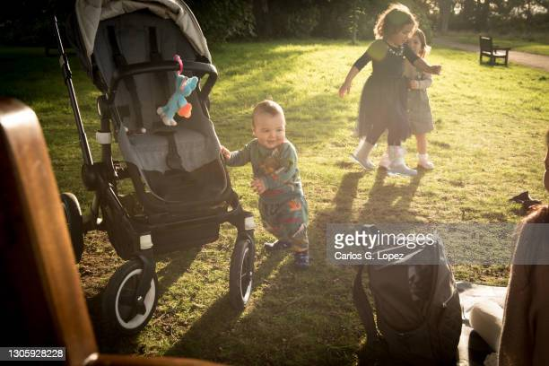 a baby stands on his feet and holds on his pram while learning to take his first steps while two toddlers play on the background in a sunny day in a public park - season 3 stock pictures, royalty-free photos & images