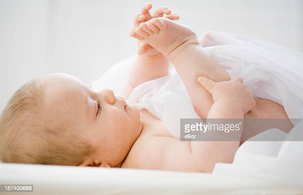 baby studying his feet. - male feet on face stock photos and pictures