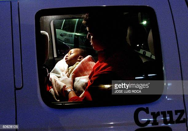 A baby Subsaharian immigrant is helped by a member of the Red Cross in the port of Tarifa Southern Spain 14 April 2005 after 66 immigrants were...