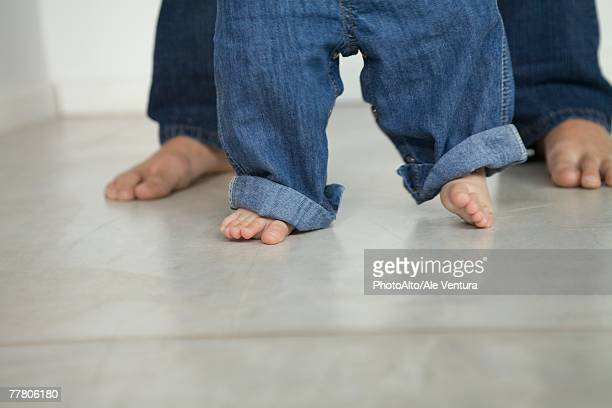 baby taking first steps, cropped view of legs - first occurrence photos et images de collection