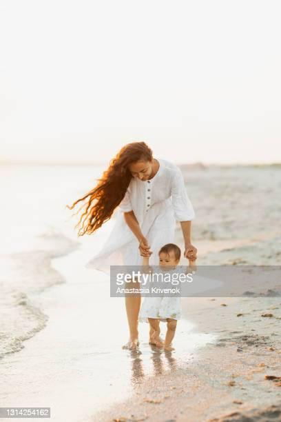 baby taking first steps on the beach, holding hands with mother. - peettante stockfoto's en -beelden