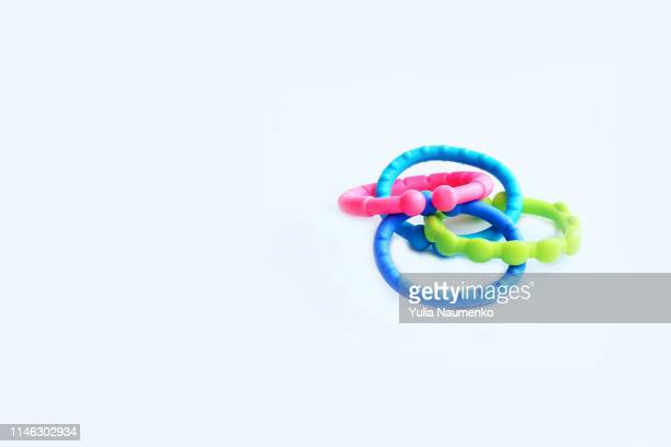 baby toy rattle in the form of a chain on a white background - toy rattle stock pictures, royalty-free photos & images