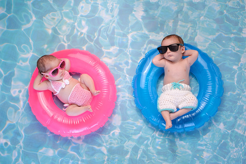 Baby Twin Boy and Girl Floating on Swim Rings 628951466