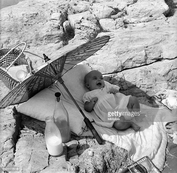 Baby under Sunshade beach pix The happy baby is 4 months old Beverley Lovelock whose mummy of the Parade Plymouth took her for a beach picnic June...