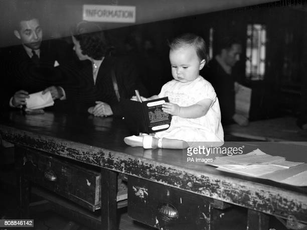 A baby waits with passport in hand for her long trip to a new life in Australia