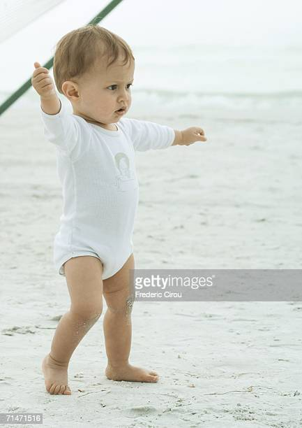 Baby walking on beach with arms outstretched