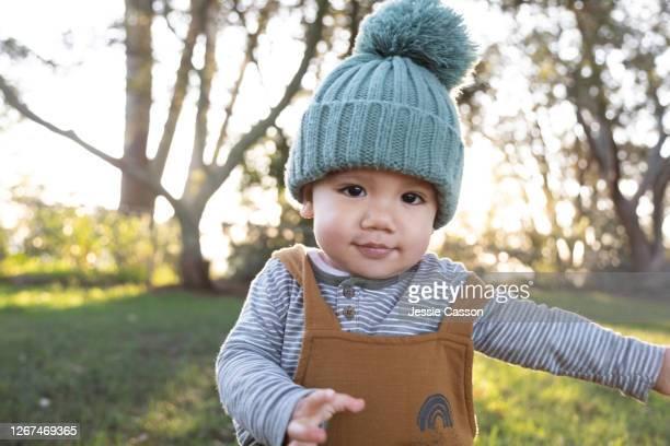 baby walking through park in beautiful light - ニット帽 ストックフォトと画像