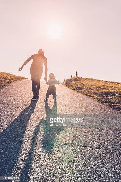 baby walking with help of its parents - first steps - vertical stock pictures, royalty-free photos & images