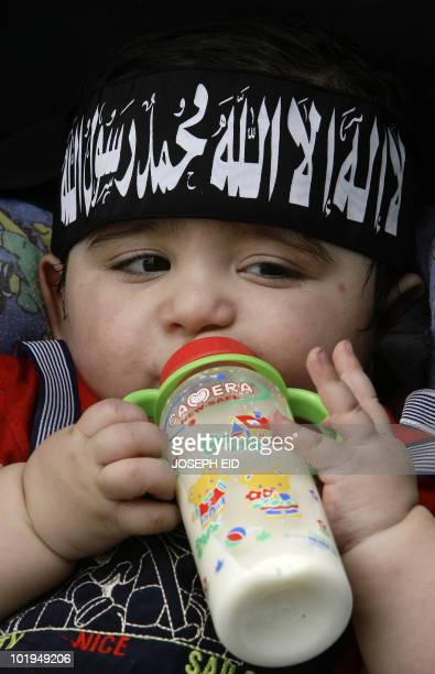 A baby wearing a headband that reads in Arabic 'There is no God but God and Mohammed is his Prophet' drinks from a bottle of milk as his parents take...