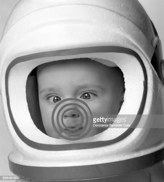 baby wearing astronaut toy helmet - constance bannister stock photos and pictures